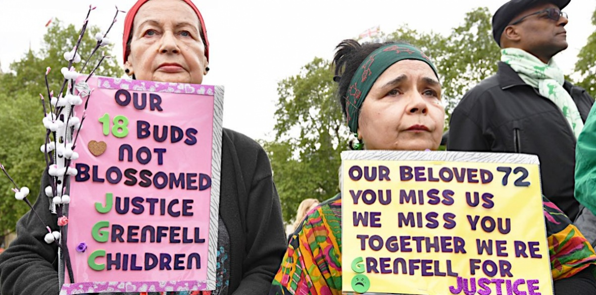 People hold placards at a Grenfell justice protest outside the British parliament on May 14 2018. Photo: John Stillwell/PA Wire