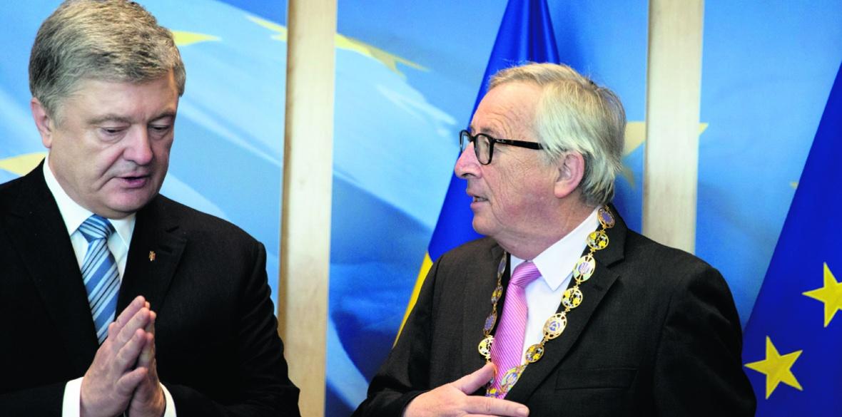 European Commission President Jean-Claude Juncker (right) receives a medal from Ukraine's President Petro Poroshenko