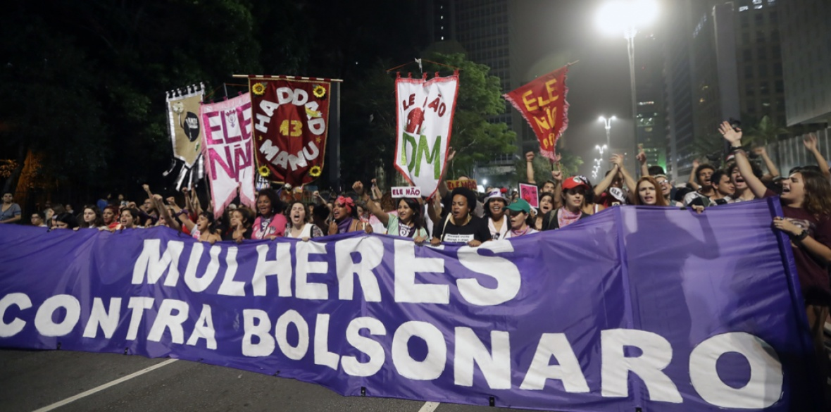 Women march holding a banner that reads in Portuguese: 'Women against Bolsonaro' during a protest against far-right presidential candidate Jair Bolsonaro on Saturday