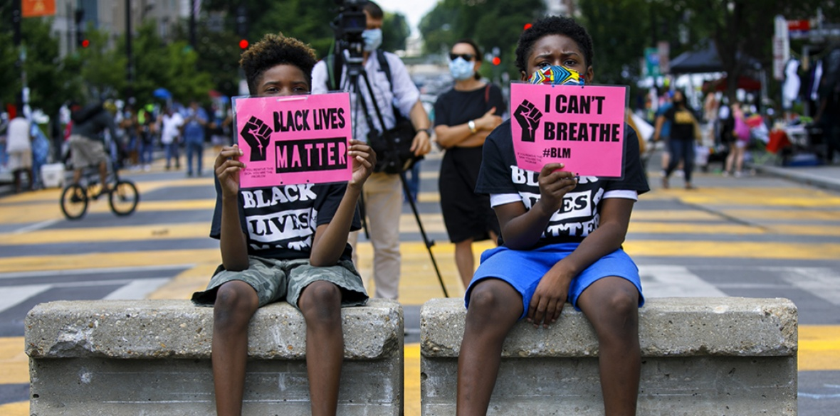 Tyshawn, 9, (left) and his brother Tyler, 11, (right) of Baltimore, hold signs saying 'Black Lives Matter' and 'I Can't Breathe' as they sit on a concrete barrier near a police line as demonstrators protest along a section of 16th Street that has been renamed Black Lives Matter Plaza, in Washington DC yesterday