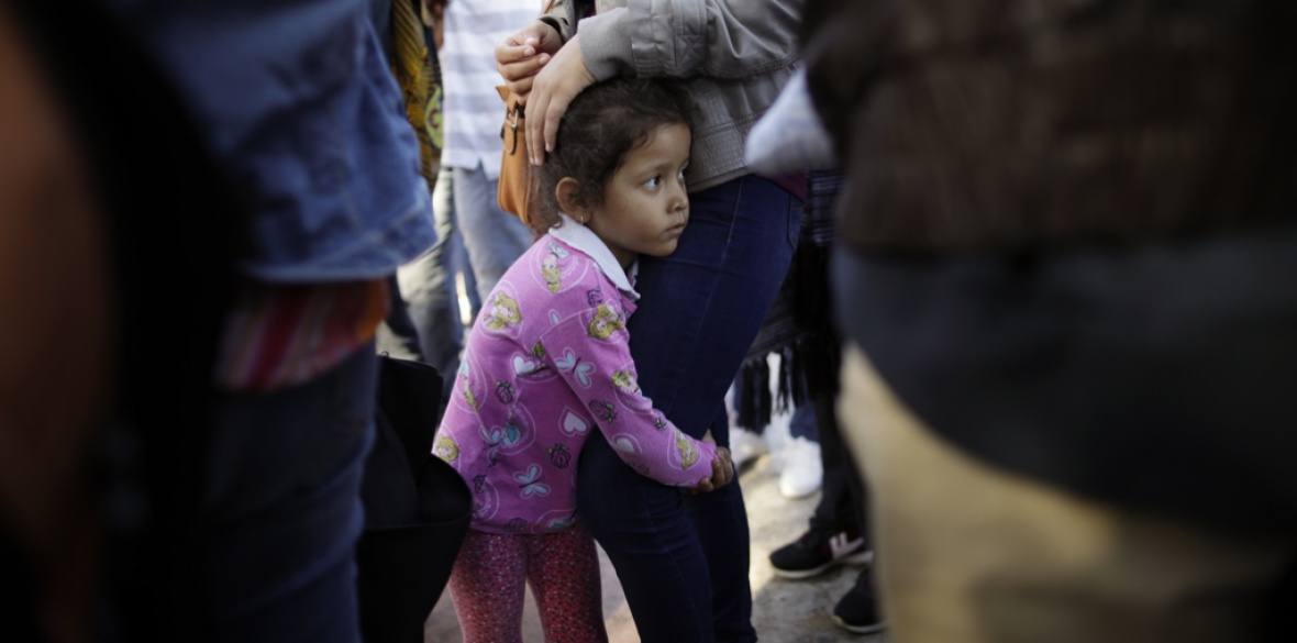 A young girl holds on to her mother as they wait with other families to request political asylum in the United States, across the border in Tijuana, Mexico