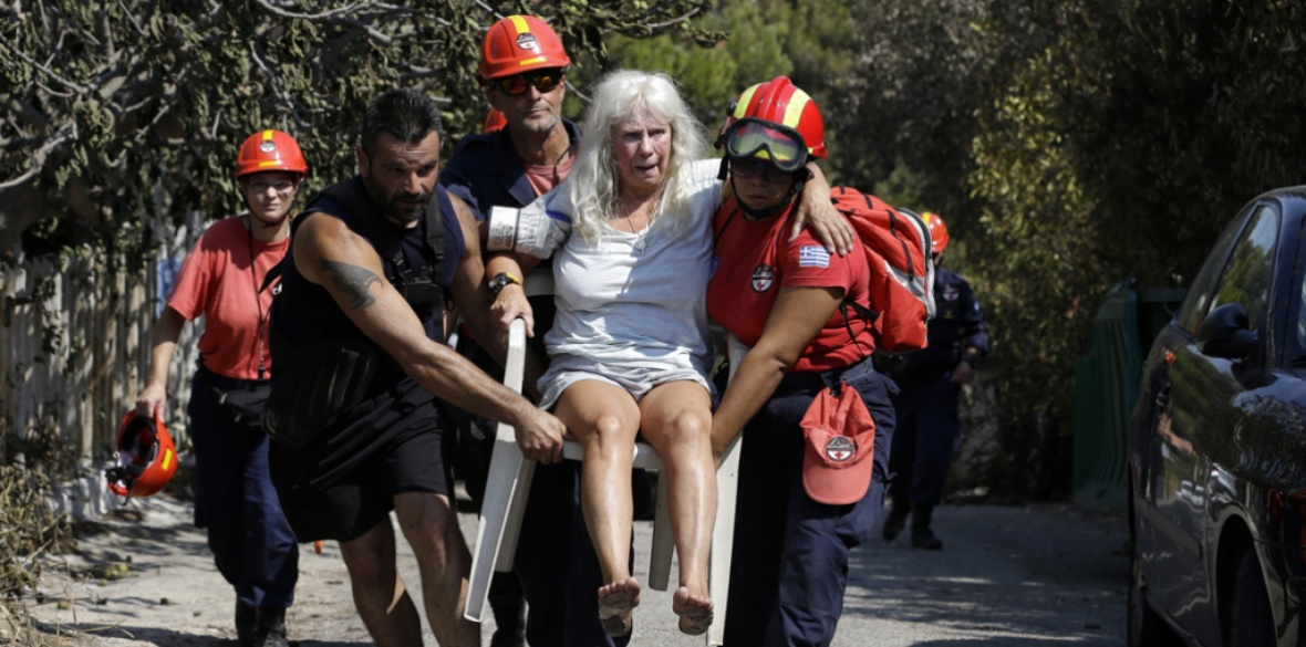 Members of a rescue team carry an injured woman in Mati, east of Athens, today. Rescue crews are searching through charred homes and cars for those still missing after the deadliest wildfires to hit Greece in decades decimated seaside areas near Athens, killing at least 80 people and sending thousands fleeing
