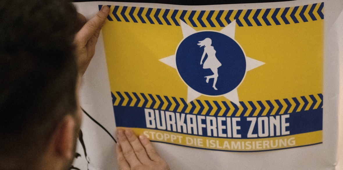 A man glues a poster reading 'burka free zone — stop Islamisation' at a meeting of the far right Alternative for Germany (AfD) party, in Neuenhagen near Berlin, earlier this month