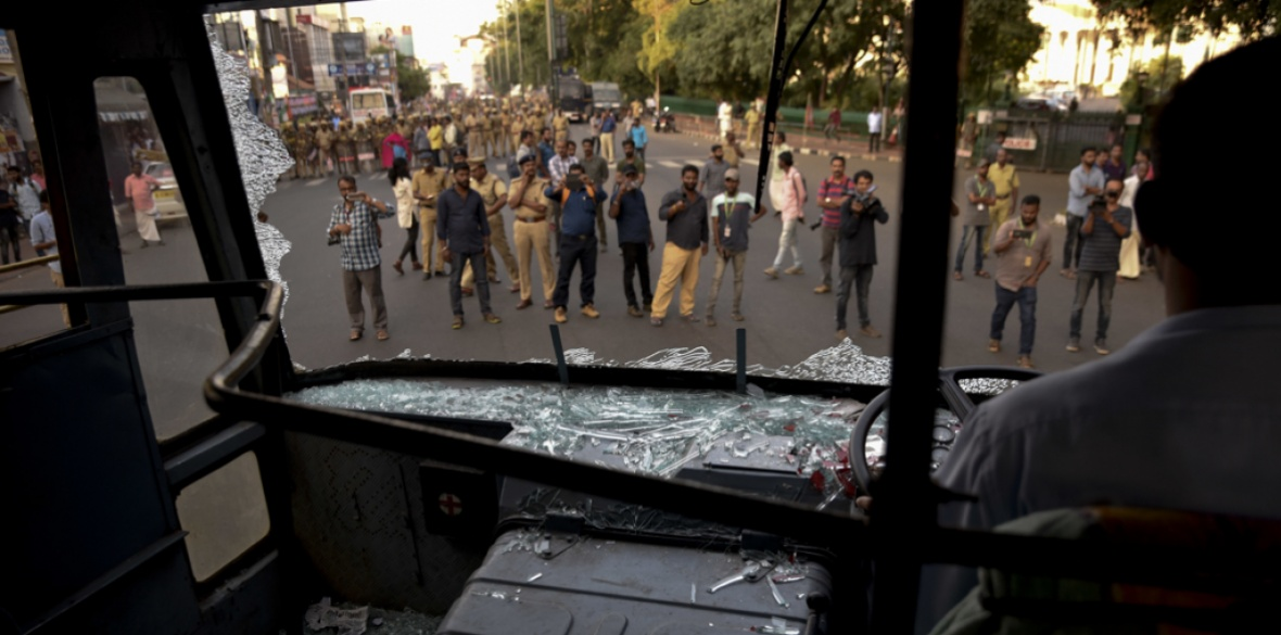 Policemen and others view state-owned buses that were vandalised as BJP supporters attack women across Kerala state in India