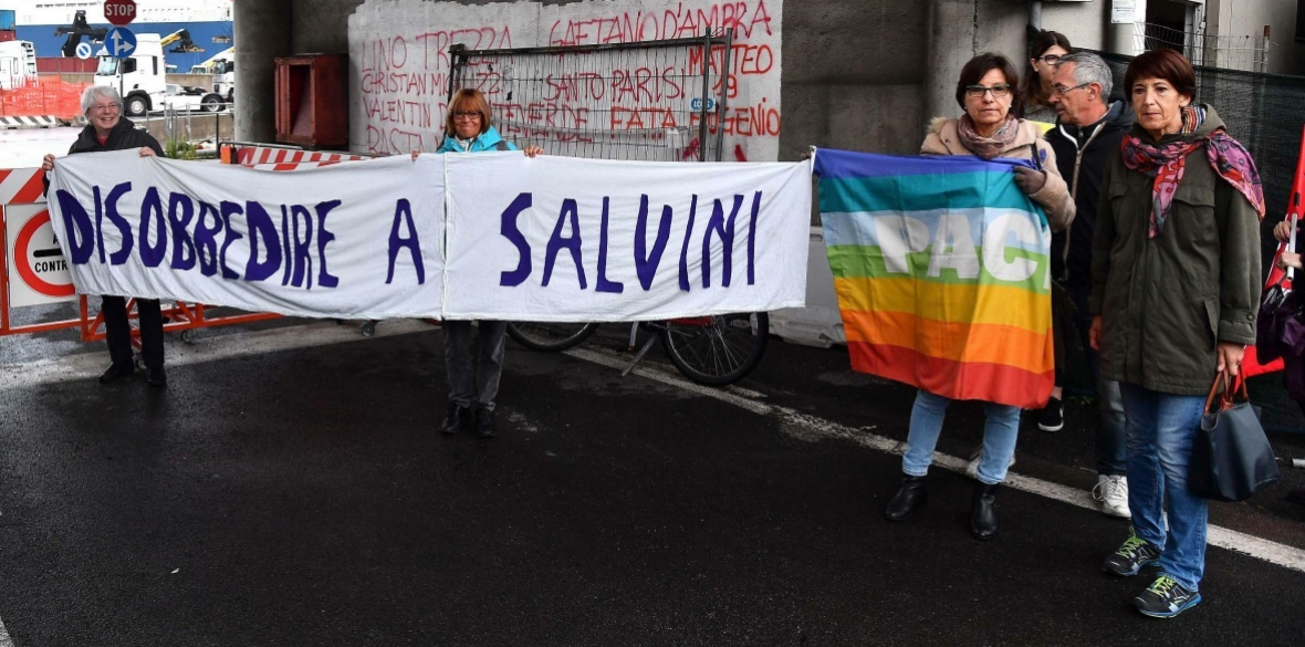 Italian activists holds up a banner which says 'Disobey Salvini' as they protest against the Saudi Arabian freighter Bahri Yanbu docked in Genoa's port in May. On the right, a peace flag