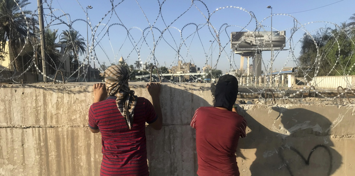 Anti-government protesters look toward the protest site area, blocked with concrete walls by Iraqi security forces in Baghdad