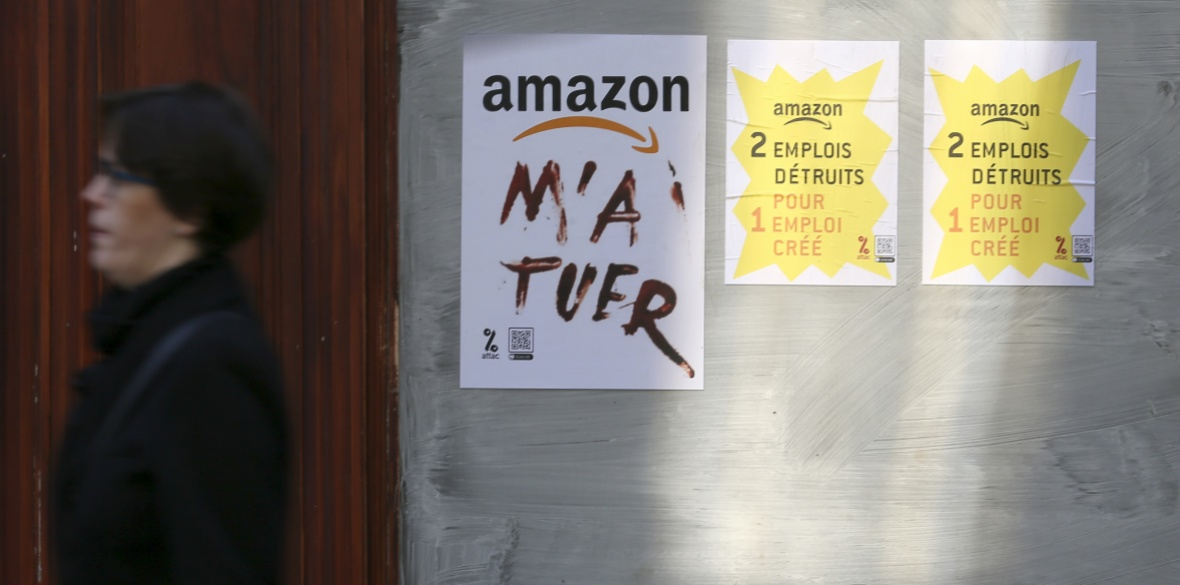 A woman walks past posters stuck by anti-Black Friday activists and reading: 'Amazon killed me' (left) and 'Amazon, 2 jobs disappear for one created' in Rennes, western France