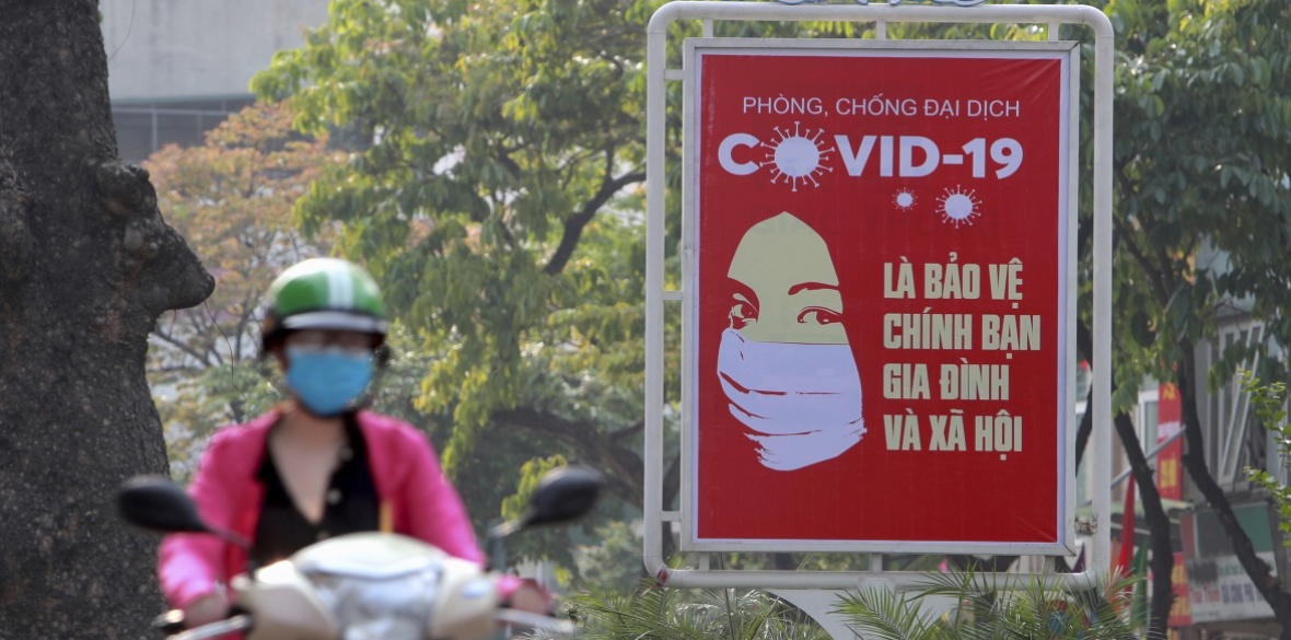 A motorcyclist drives past a poster calling people to take care of their health against coronavirus in Hanoi, Vietnam