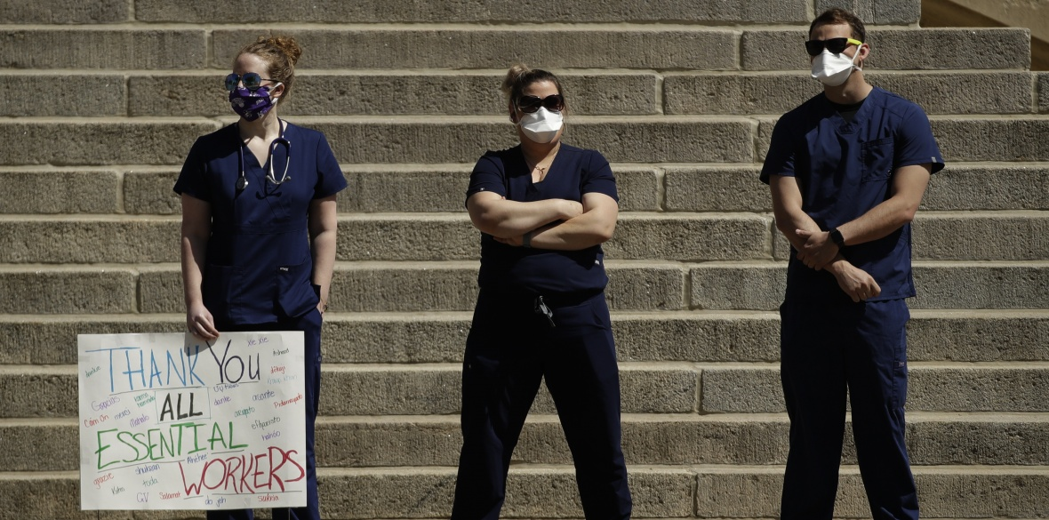 Nurses stand before the steps of the Statehouse as they counter-protest a rally against stay-at-home orders put into place due to the Covid-19, in Kansas, USA yesterday