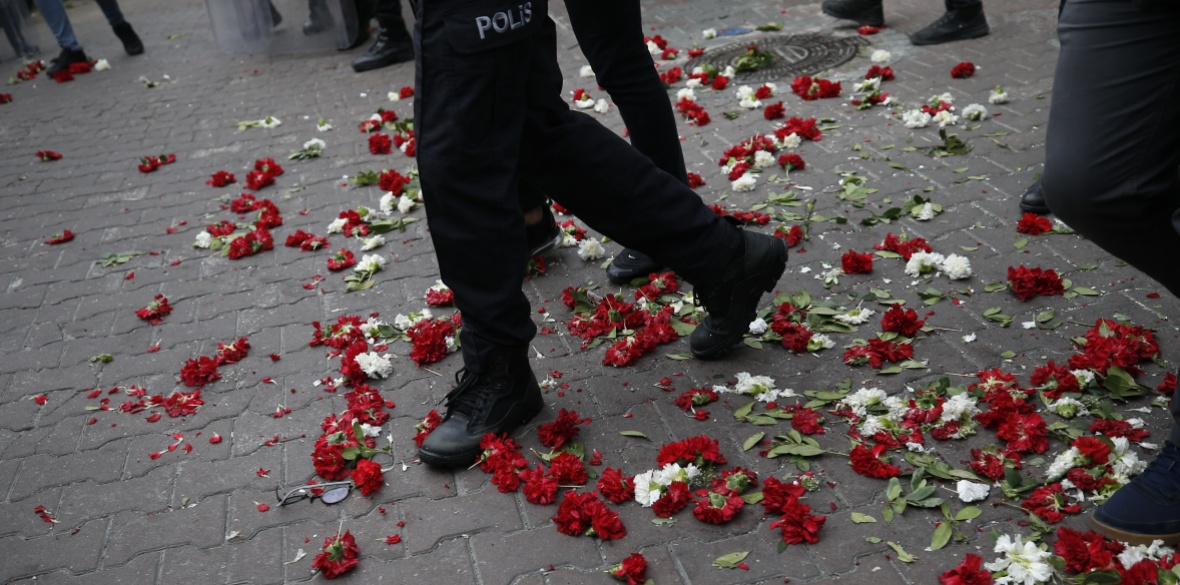 Turkish police officers trampling carnations left by demonstrators during banned May Day protests in Istanbul