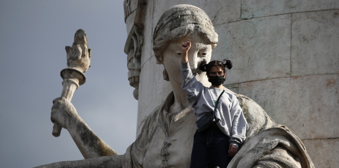 A demonstrator clenches her fist as she stands on a statue on the Place de la Republique during a rally against racism in Paris, France yesterday