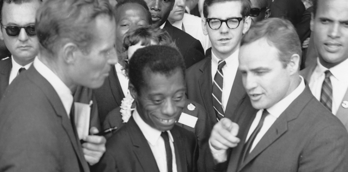 James Baldwin, flanked by actors Charlton Heston (left) and Marlon Brando at the Civil Rights March on Washington in 1963. Photo US Information Agency, Press and Publications Service