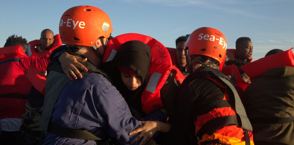 Sea Eye's crew pull refugees from an unseaworthy boat in the central Mediterranean