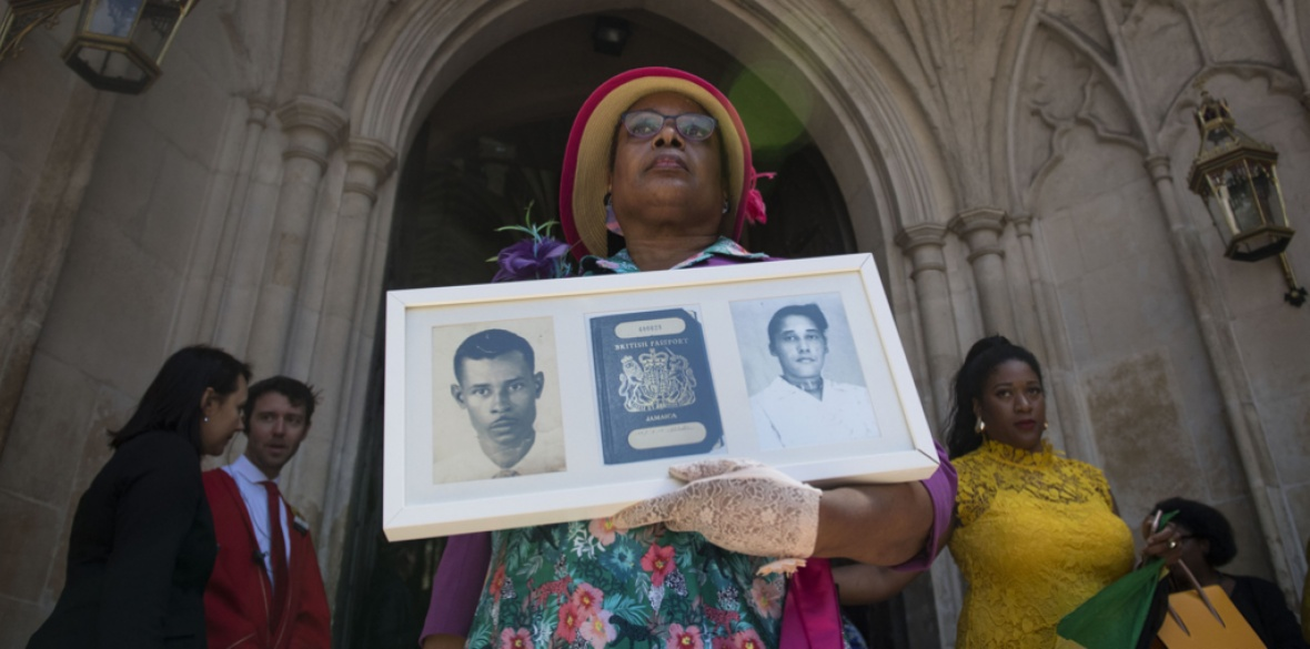 Andria Marsh holding a photo of her parents, who arrived on the ship Windrush, after the service of thanksgiving at Westminster Abbey in London last month