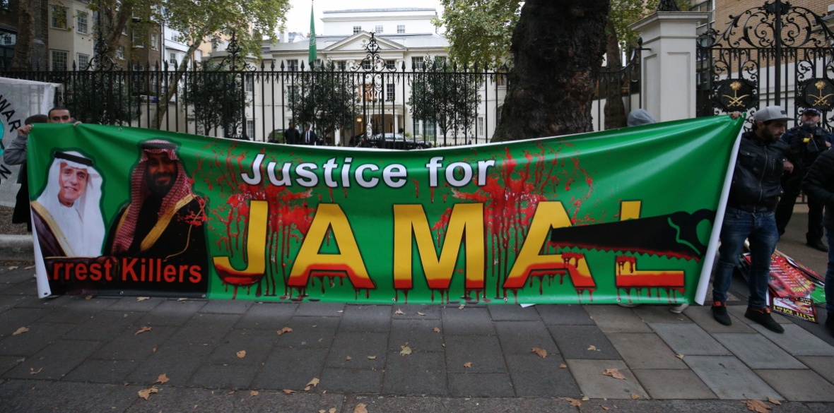 People hold a banner demanding justice for Jamal Khashoggi during a protest outside the Saudi Arabian embassy in central London in October