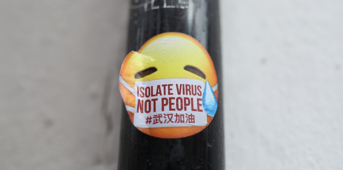 A sticker against anti-Chinese racism is seen showing the words 'Isolate virus, not people', in China Town, Leicester Square, London