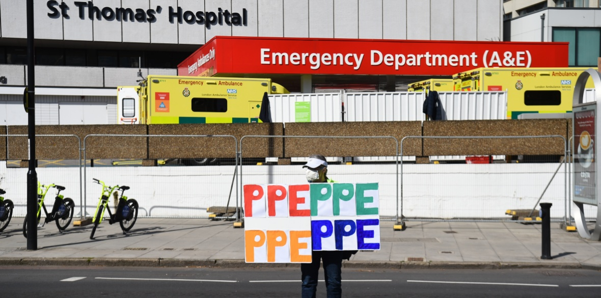 A demonstrator holds signs saying PPE outside St Thomas' Hospital in Central London where Prime Minister Boris Johnson is in intensive care as his coronavirus symptoms persist