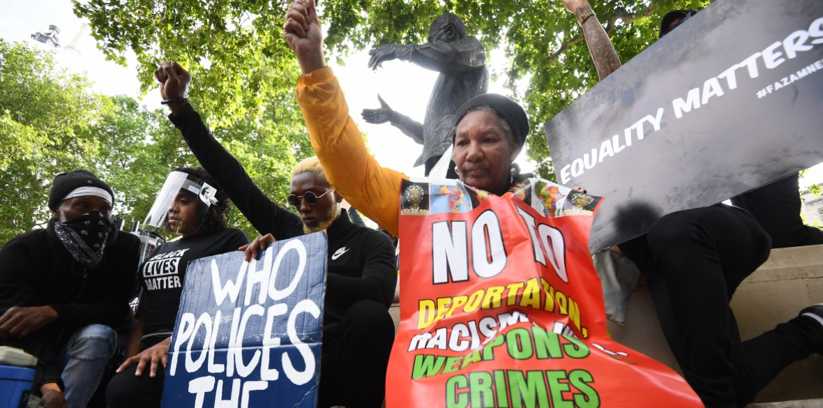 People kneeling during a minute silence during a rally at the Nelson Mandela statue in Parliament Square, London, to commemorate George Floyd as his funeral takes place in the US following his death on May 25 while in police custody in the US city of Minneapolis