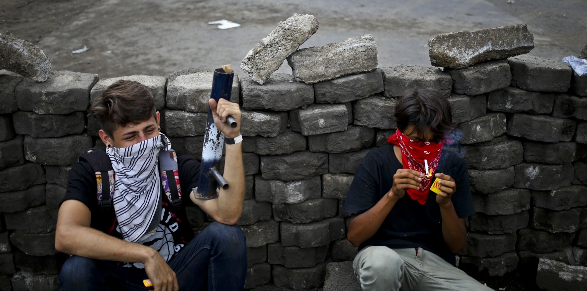 Nicaraguan anti-government protesters hide behind a brick roadblock, one of them wielding a home-made mortar weapon