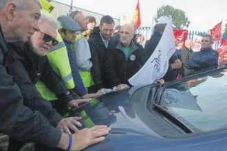The picket confronts a car as it attempts to push through them