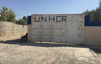 The letters U, N, H, C, and R on a gate at the refugee camp
