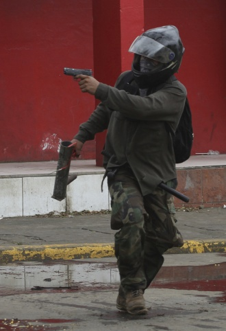 A man aims a pistol at police in during clashes in Masaya, Nicaragua, on Saturday