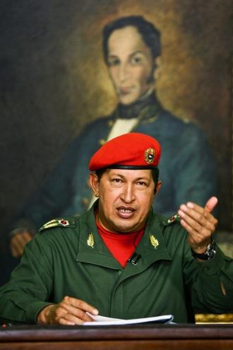 Chavez addresses an audience  under a portrait of revolutionary leader Simon Bolivar