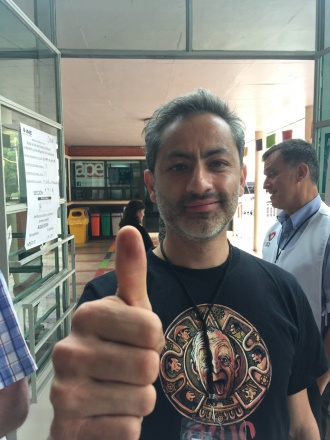 Louis Lemus shows the indelible ink stamped on his thumb after voting