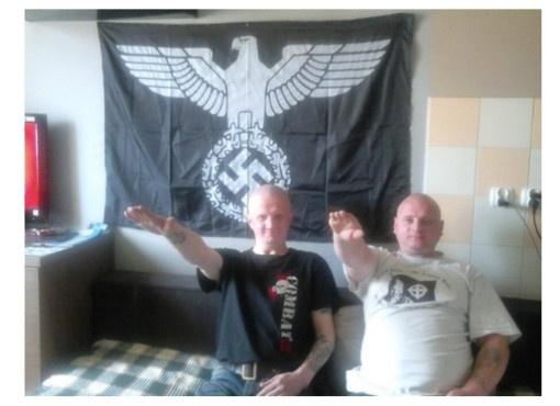 Tomasz Gawdziakowski (left) sieg heils in front of a nazi flag