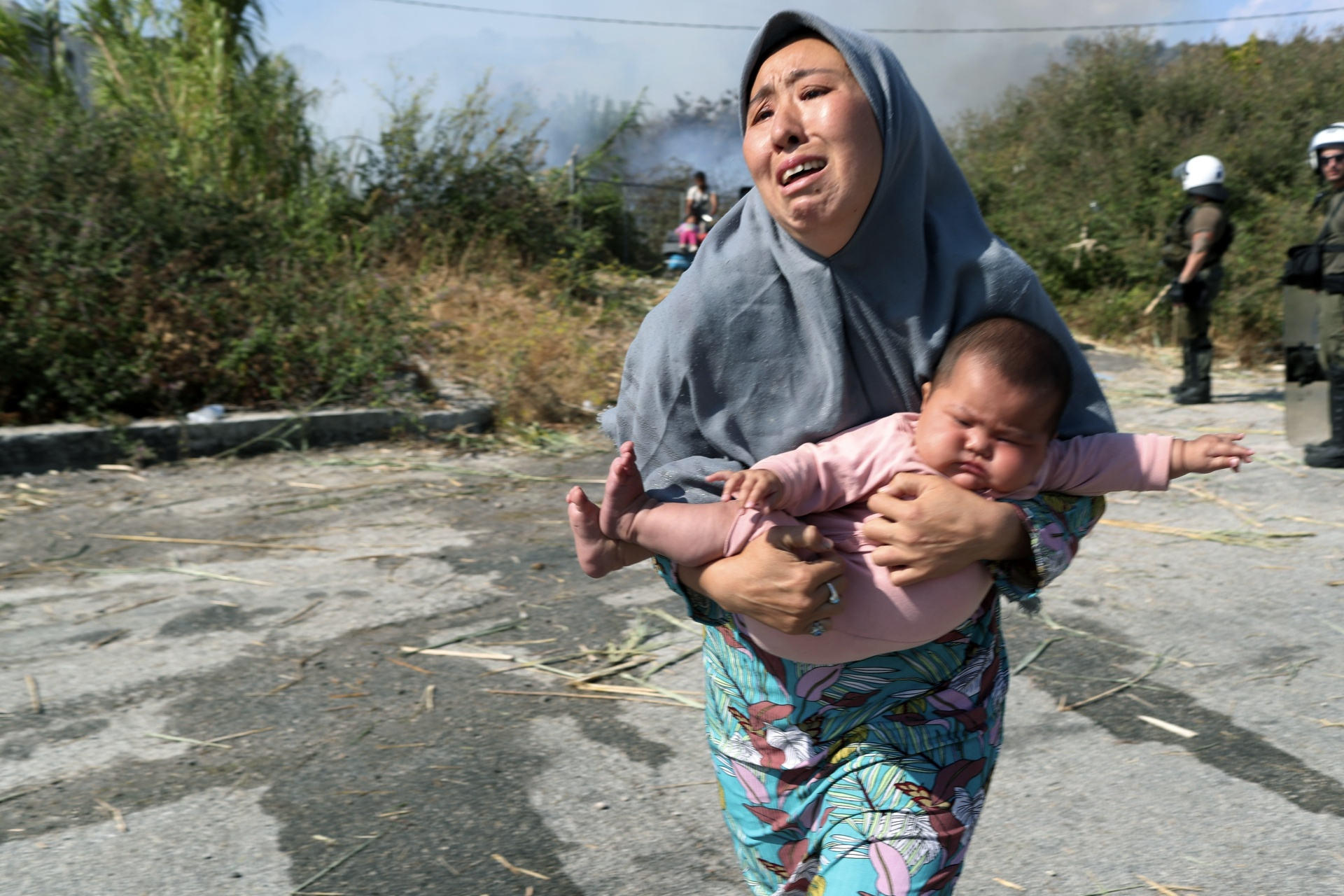 A refugee holds her baby as she runs to avoid a small fire in a field near Mytilene town, on the northeastern island of Lesbos, Greece
