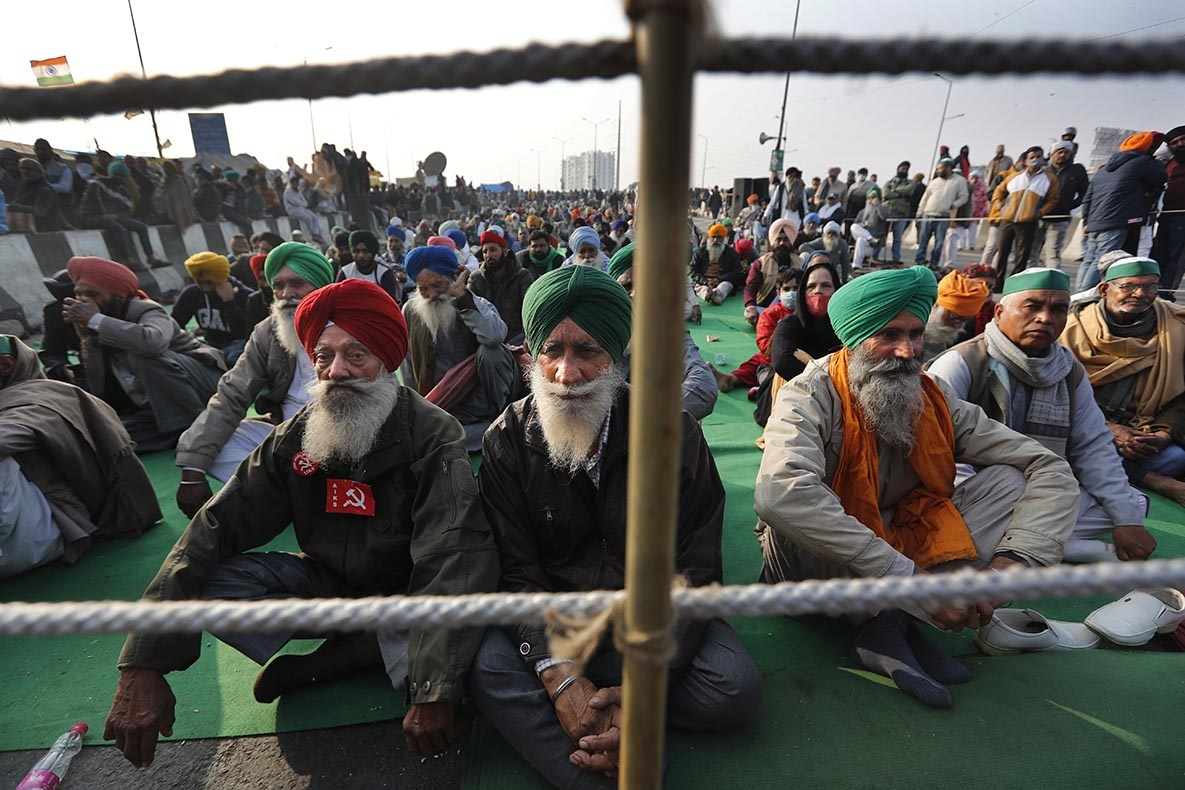 Indian farmers listen to a fellow farmer speak as they block a highway in protest against new farm laws at the Delhi-Uttar Pradesh state border, on the outskirts of New Delhi, India