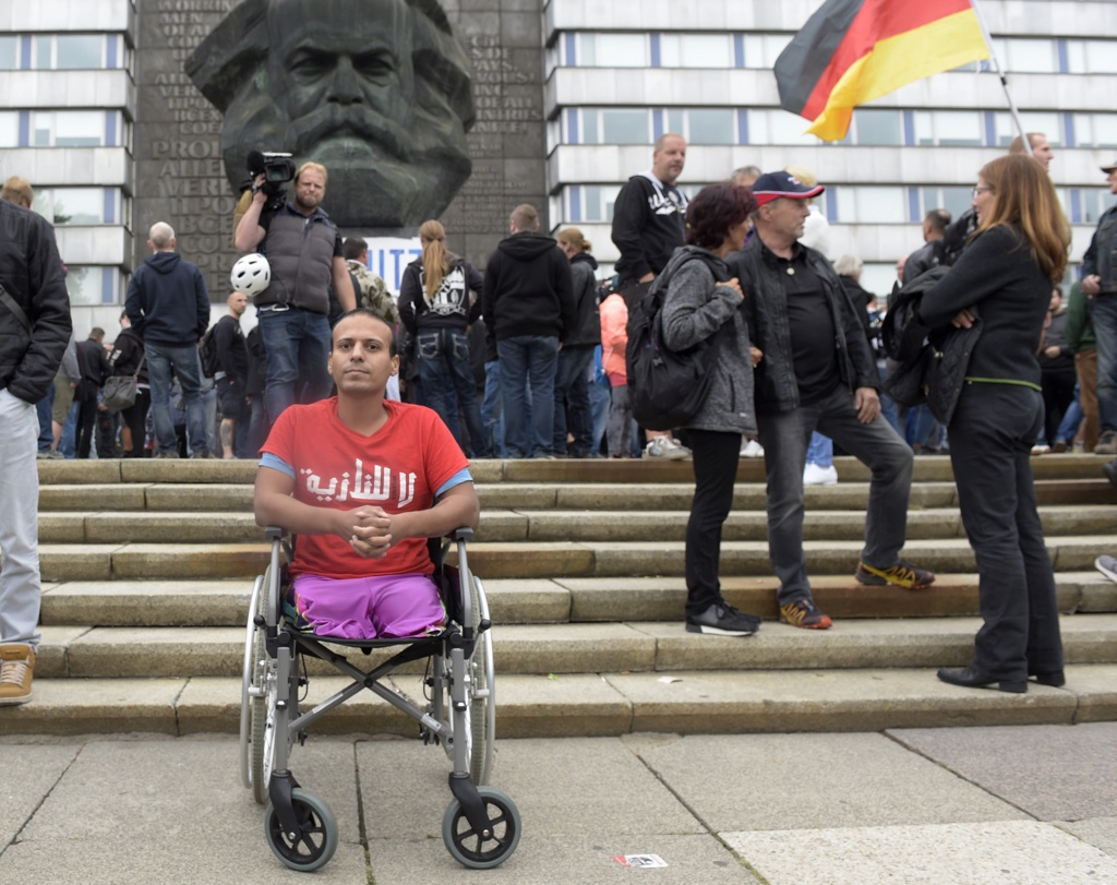 A man wears a t-shirt with the Arabic writing 'No Nazis' as he sits in a wheelchair in front of the Karl Marx statue in Chemnitz, eastern Germany, yesterday