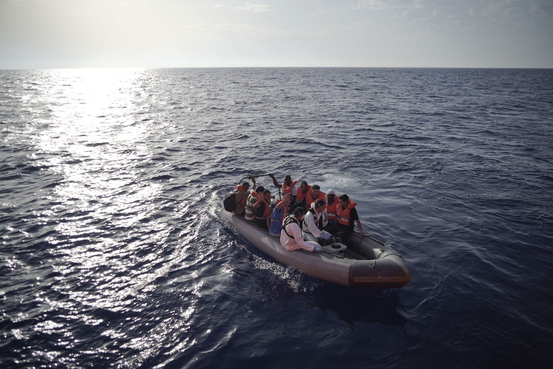 Members of the Maltese Armed Forces take a group of migrants to a Maltese military ship in the Mediterranean Sea