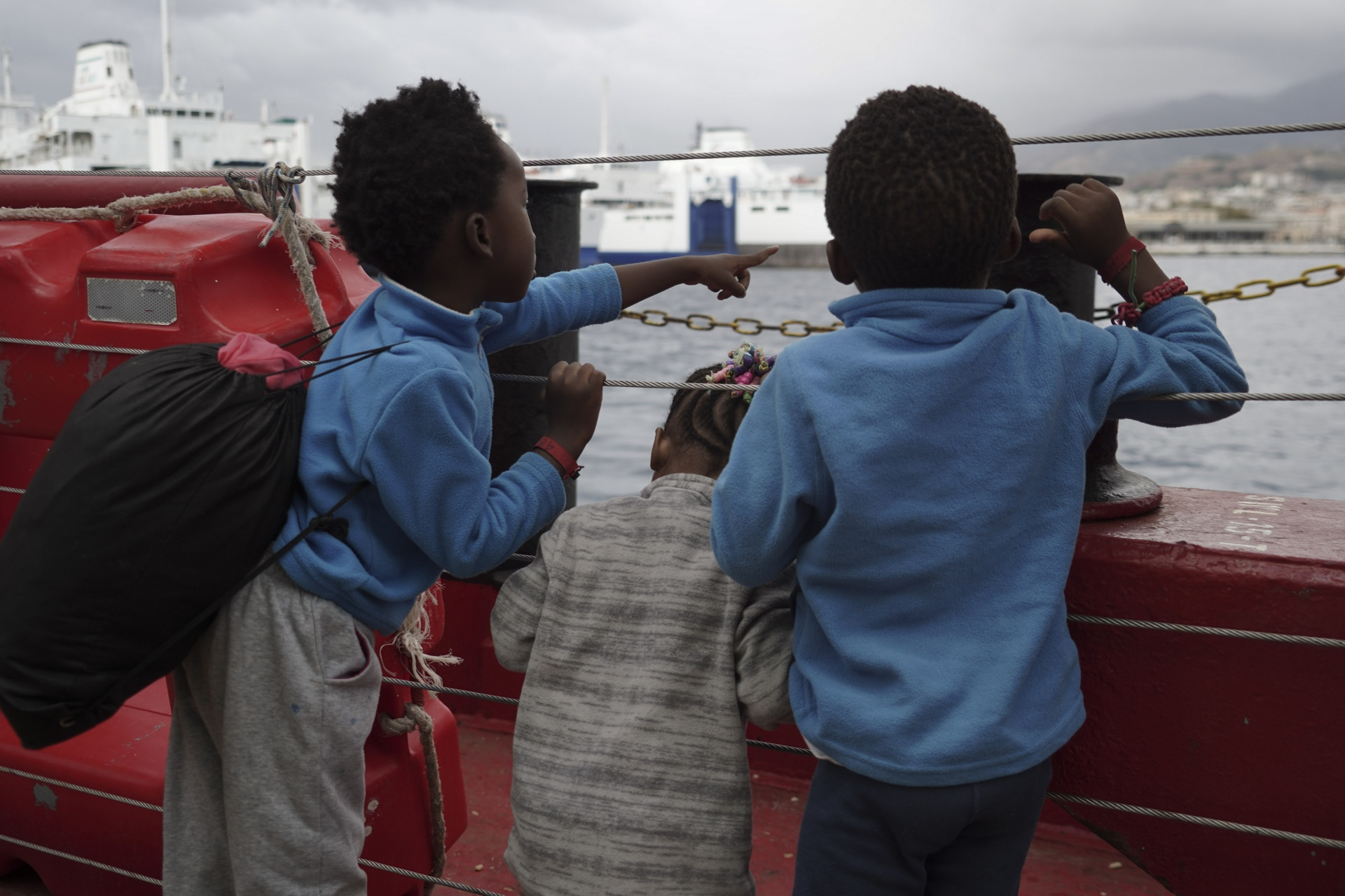 Children wave at a boat from aboard the Ocean Viking as it reaches the port of Messina, Italy