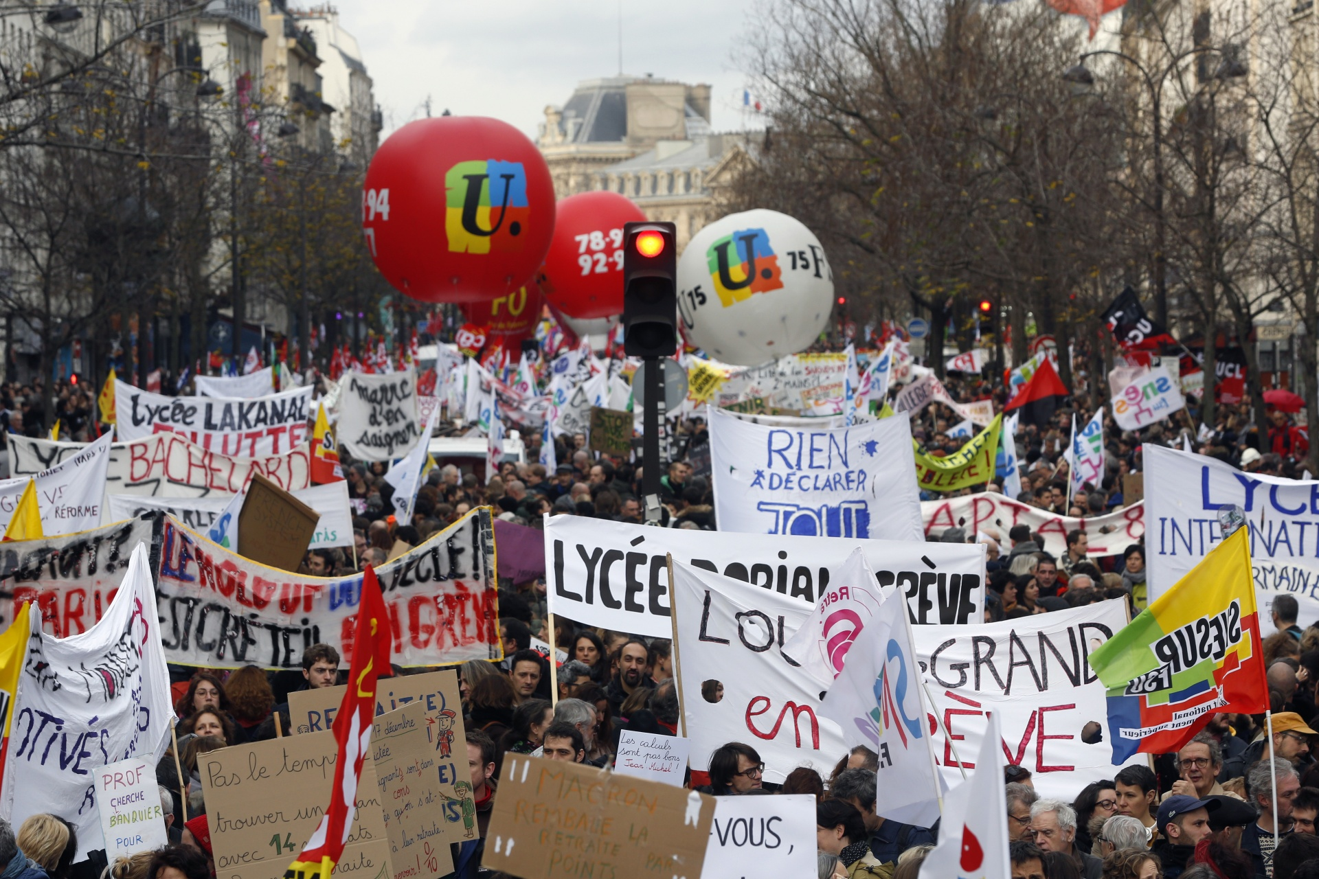 Demonstrators march with banners and union flags during a protest against pension reform plans in Paris