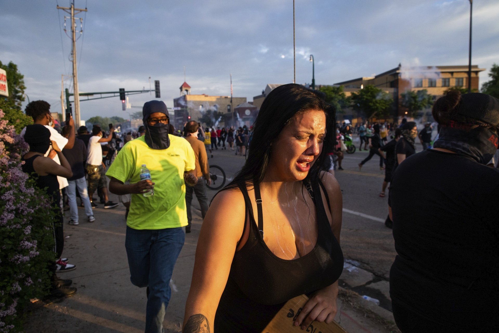 People run away from tear gas fired by Minneapolis police outside the 3rd Precinct building during protests