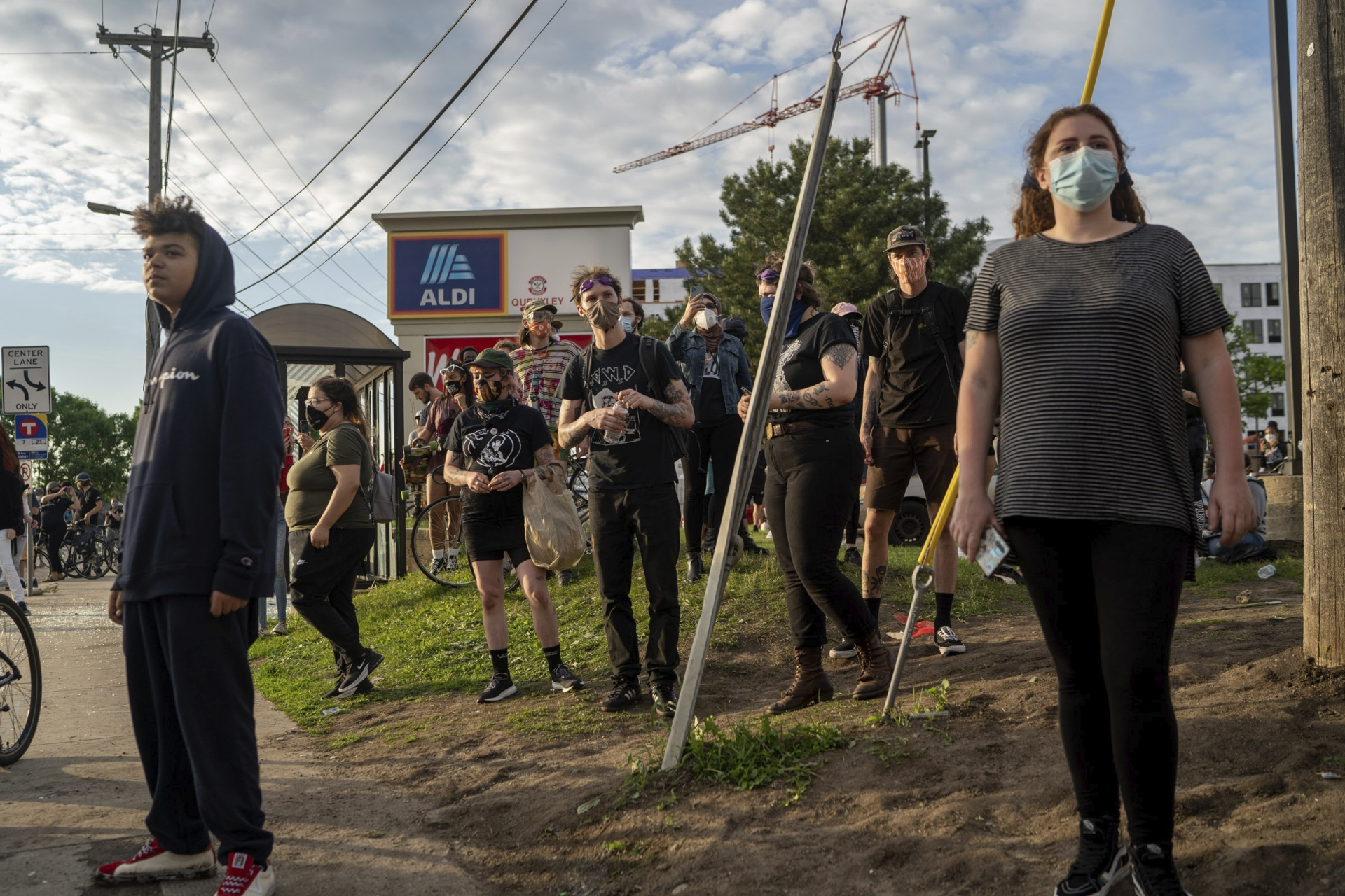 Protesters watch from a distance as police and other protesters face off during protests