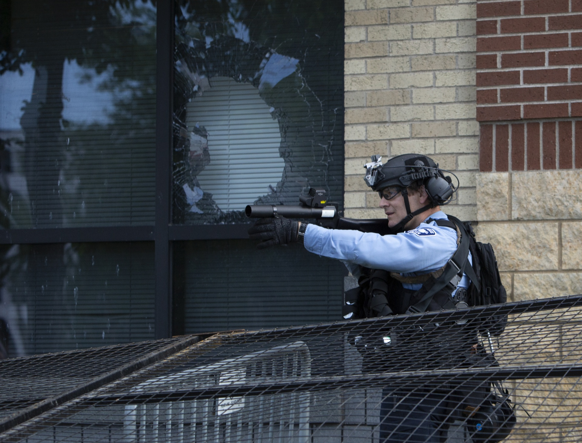 A Minneapolis police officer points a gun that fires projectiles outside the department's 3rd Precinct building
