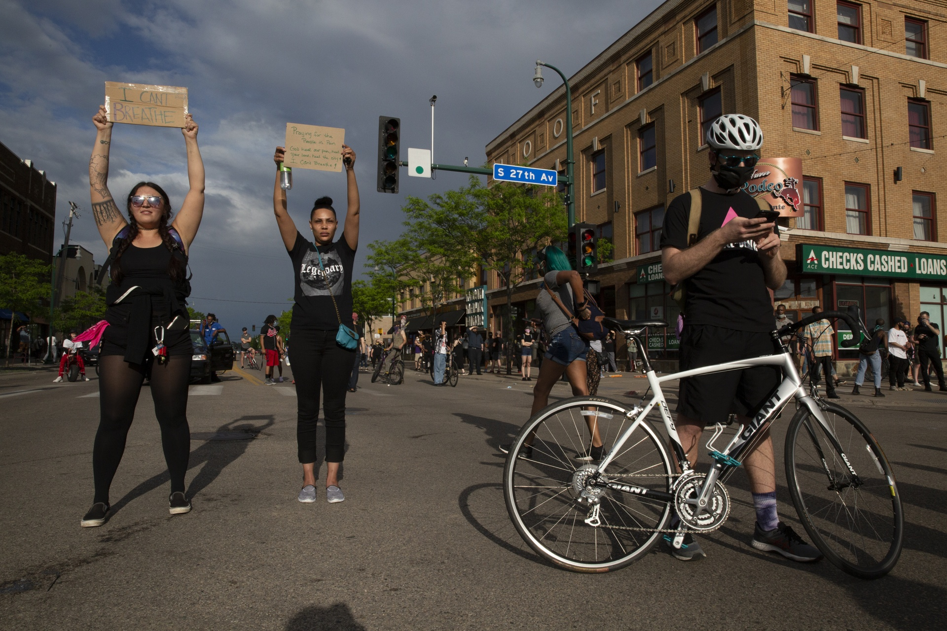 Protesters stand along Lake Street during a protest yesterday in Minneapolis against the death of George Floyd in Minneapolis police custody