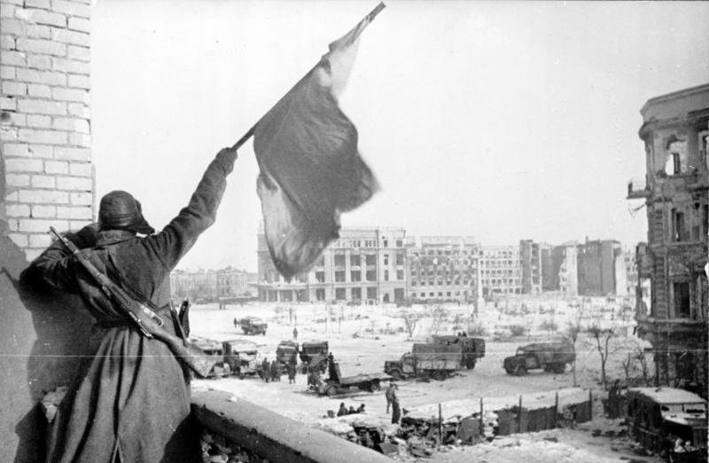 A Soviet soldier waving the Red Banner over the central plaza of Stalingrad in 1943