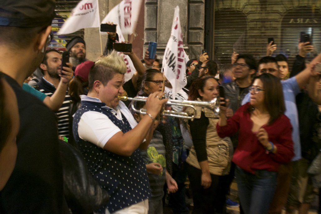 A man plays the trumpet as people celebrate Lopez Obrador's victory on Francisco Modero Avenue in central Mexico City
