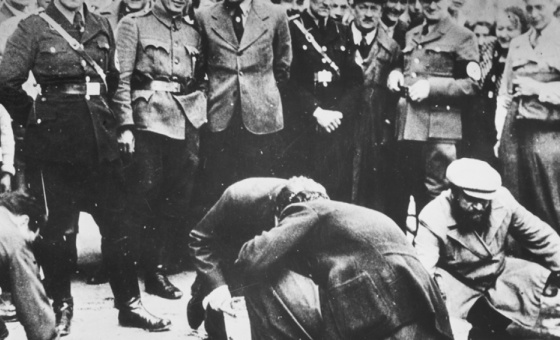 Austrian Nazis and local residents look on as Jews are forced to get on their hands and knees and scrub the pavement in March 1938