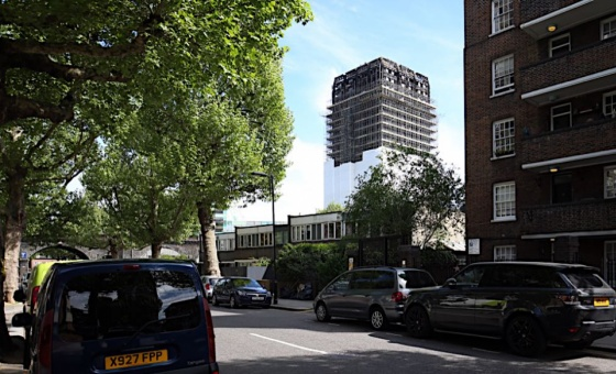 A partially covered-up Grenfell Tower is seen from a nearby residential street in west London.