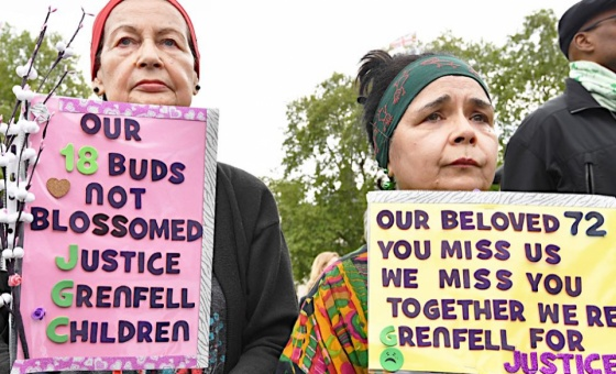 People hold placards at a Grenfell justice protest outside Parliament on May 14